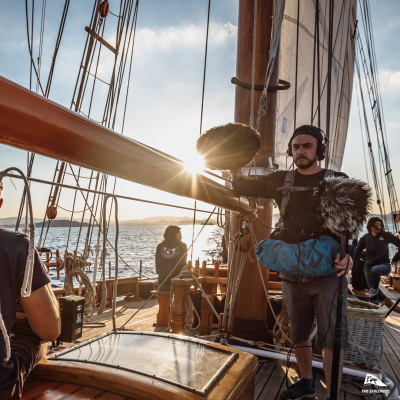 Sunrise out at sea on «Le Don du Vent» with The Explorers 💥 Please meet Sylvain in the foreground, our sound engineer. On shot, he's capturing ambient sounds in the middle of the Mediterranean Sea 🐦🌊🌬 - 📸 © @valentinpacaut / @theexplorersofficial